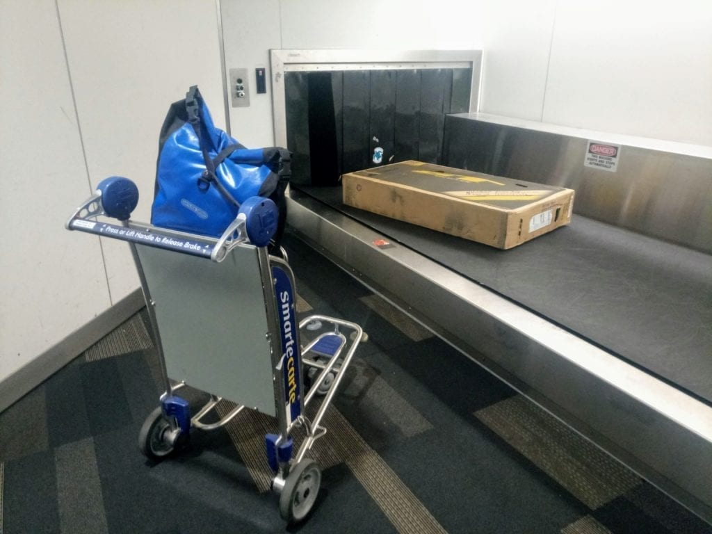 Bicycle box on luggage conveyor belt at airport