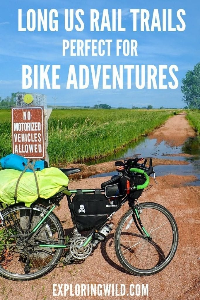 Loaded touring bicycle leaning against trail sign on Cowboy Trail with text overlay: Long US rail trails, perfect for bike adventures