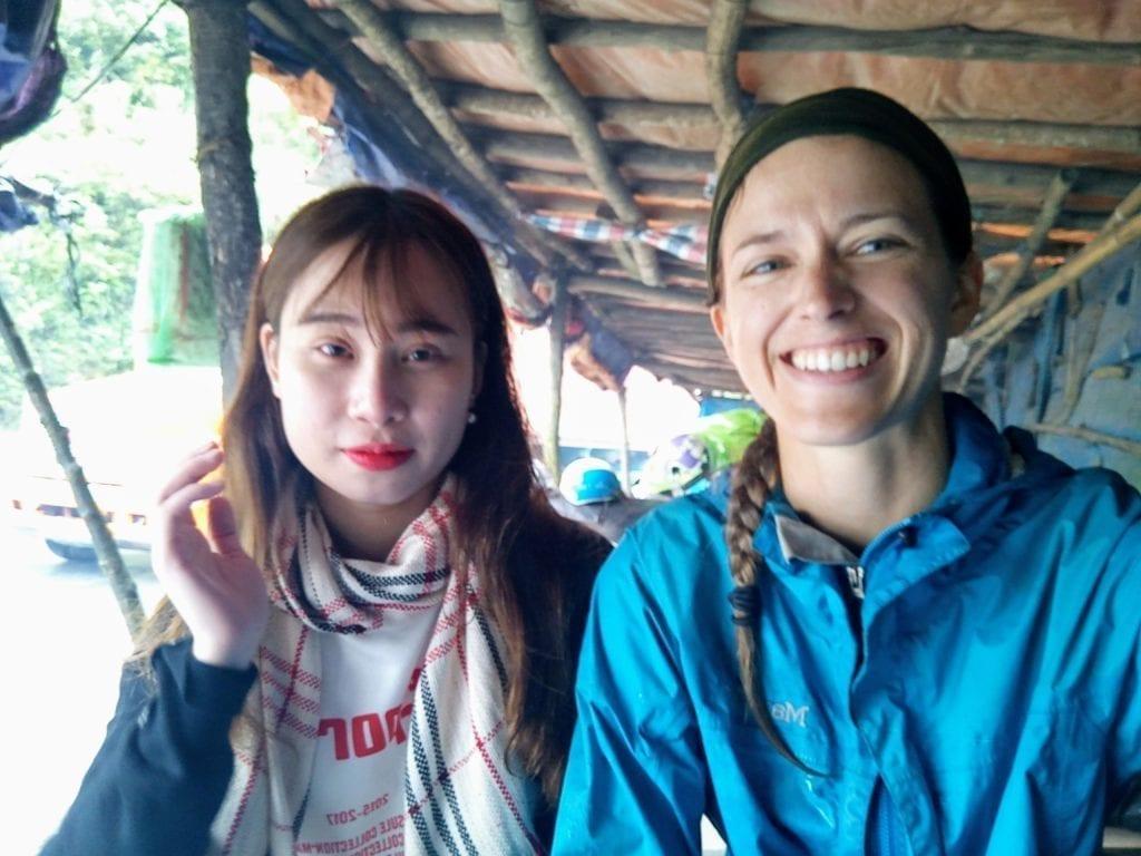 Traveler in blue rain jacket sitting under shelter with Vietnamese woman in northern Vietnam