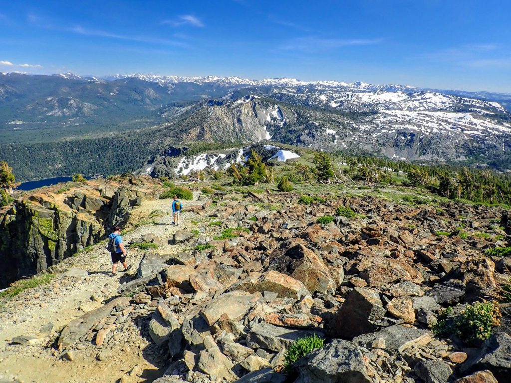 Two hikers descending rocky trail from Mount Tallac with Desolation Wilderness in the background