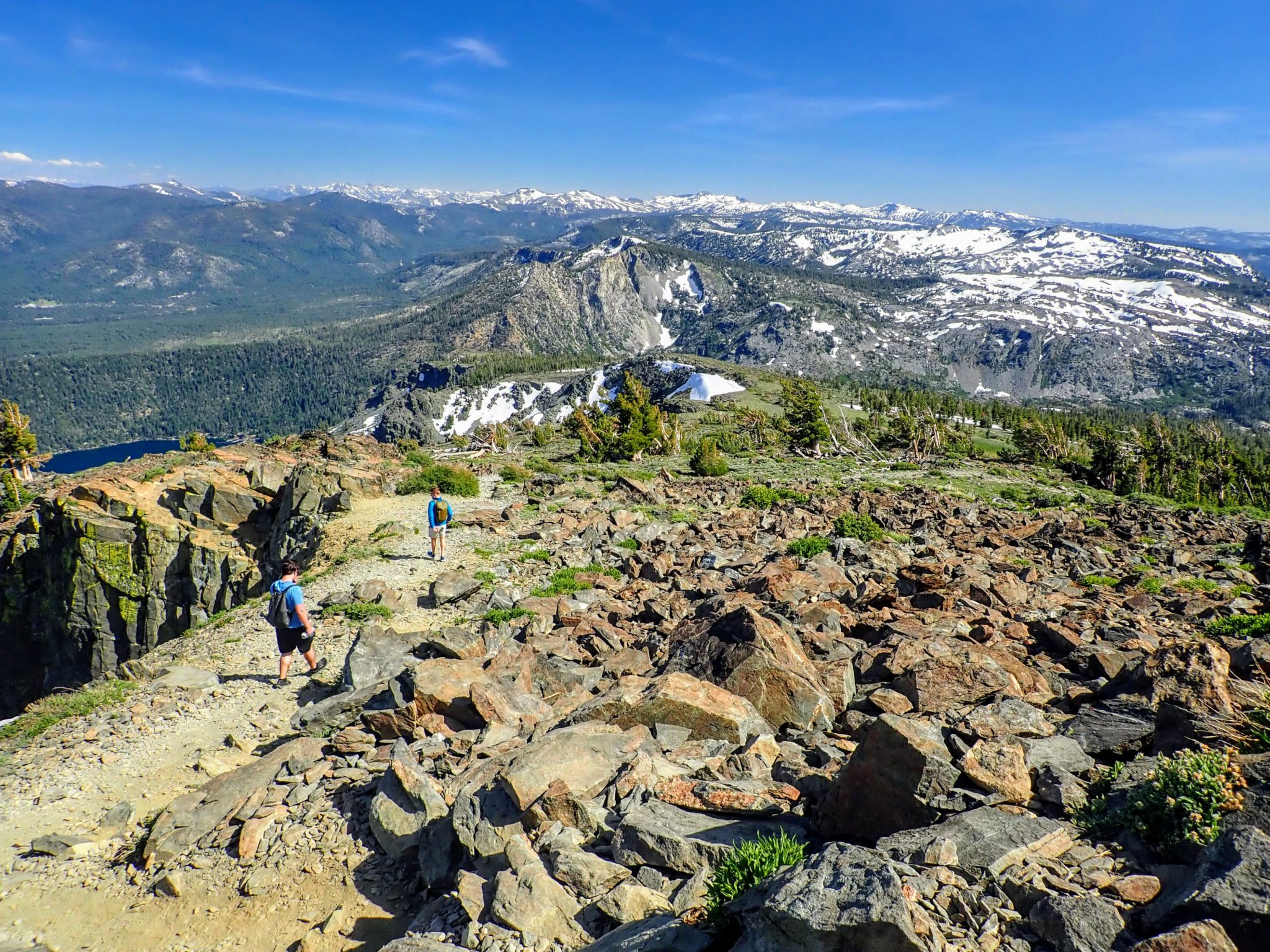 Two hikers descending rocky trail from Mt. Tallac, with Desolation Wilderness in background