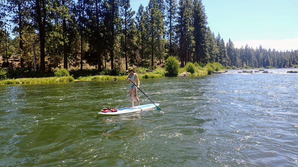 SUP boarder on the Deschutes River on vacation near Bend, Oregon