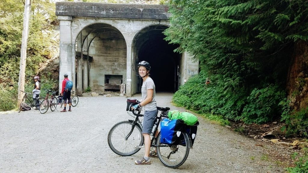 Touring cyclist in front of old railway tunnel on the Palouse to Cascades Trail
