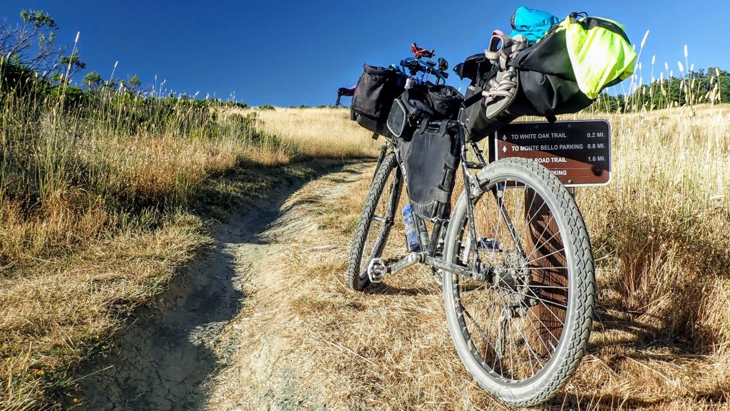 Loaded bikepacking bike leaning against trail sign on Monte Bello Preserve singletrack