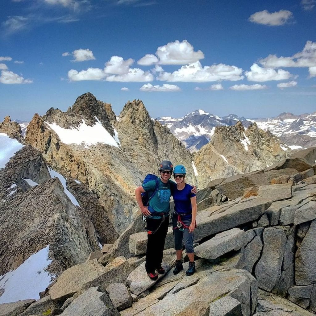 Couple of climbers at summit of Sill with rugged Palisades ridge behind
