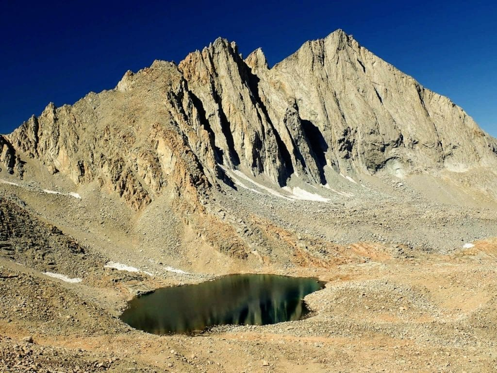 View of rugged granite Mount Tyndall and an alpine lake