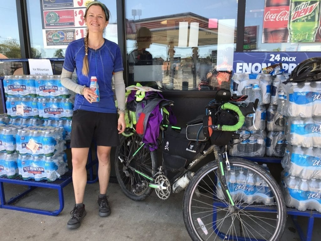 Touring cyclist drinking chocolate milk outside a gas station in Ohio