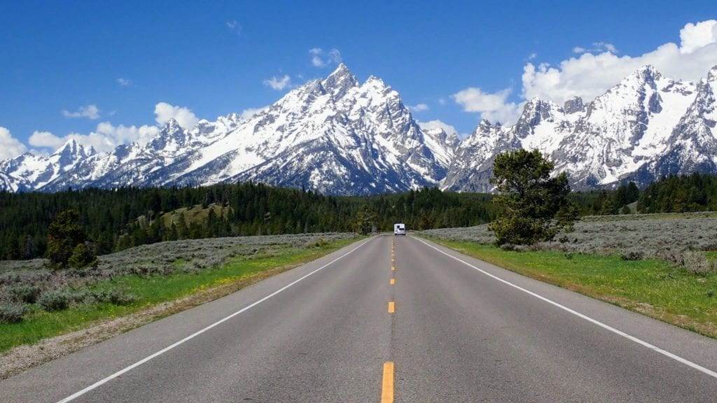 Road heading toward snow-capped mountains in Grand Teton National Park
