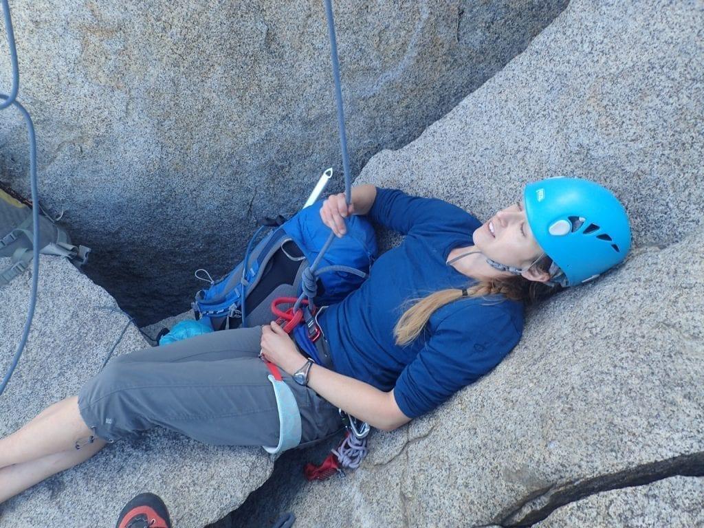 Tired climber lies on rock.