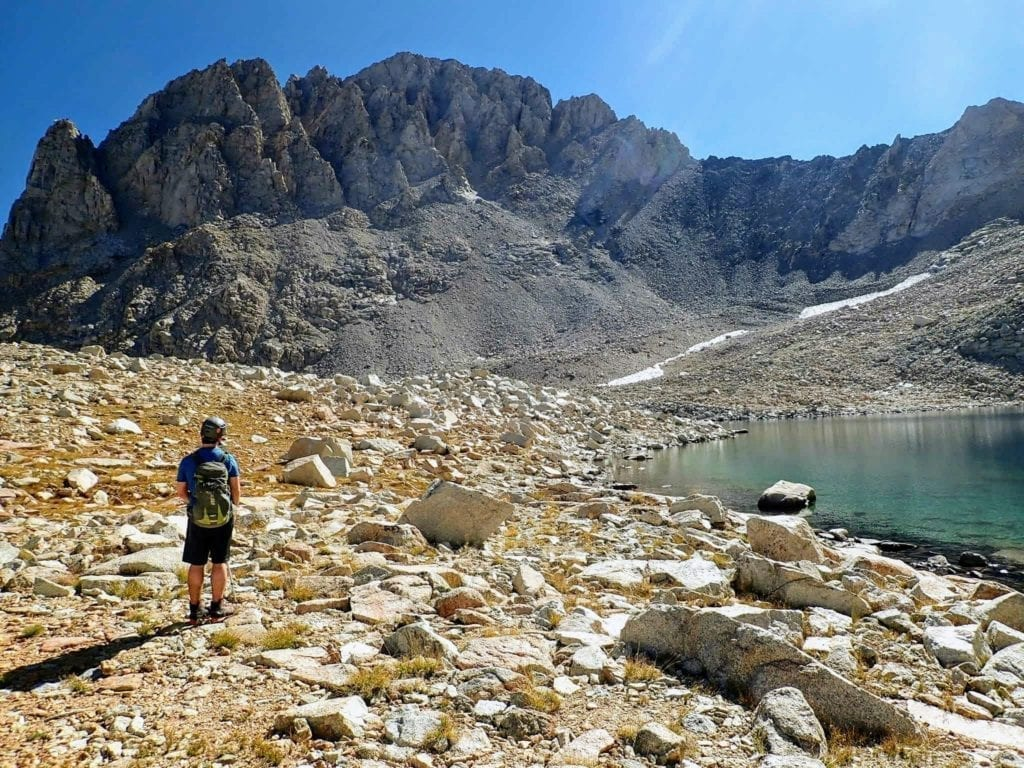 Hiker looks up at Mount Williamson from small alpine lake.