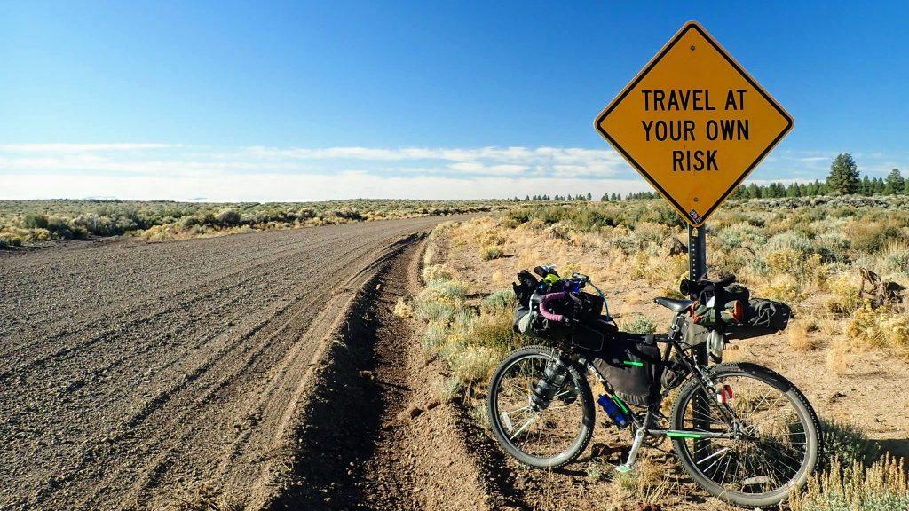 Bikepacking bike leaning against road sign on remote gravel road