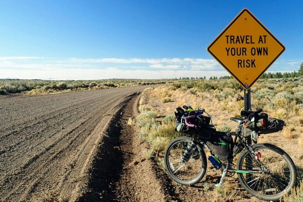 Bikepacking bike leaning against road sign on remote gravel road