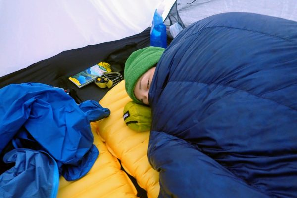 Backpacker huddled in sleeping quilt