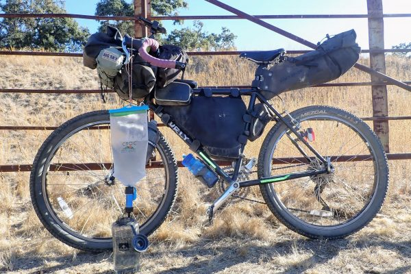 Gravity water filter hanging from bike handlebars on bikepacking trip