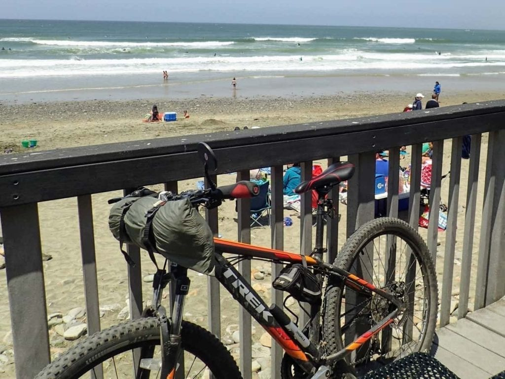 tent strapped to handlebars of mountain bike at beach