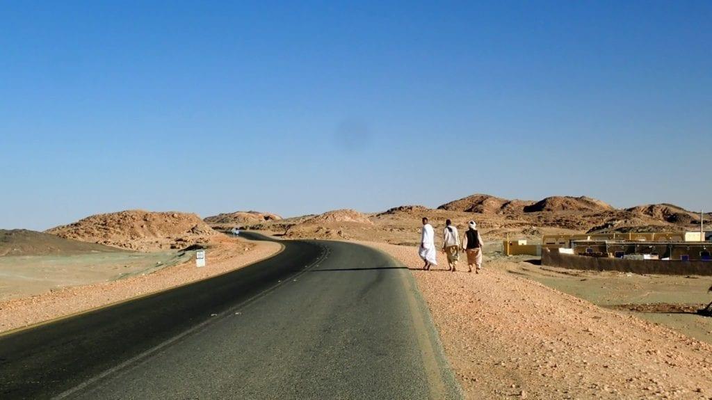 Men walk along a desert highway in northern Sudan