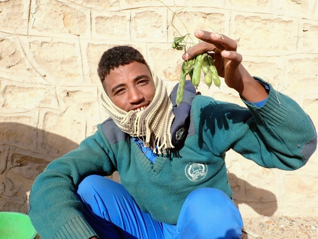 Sudanese man holds up beans used to make ful