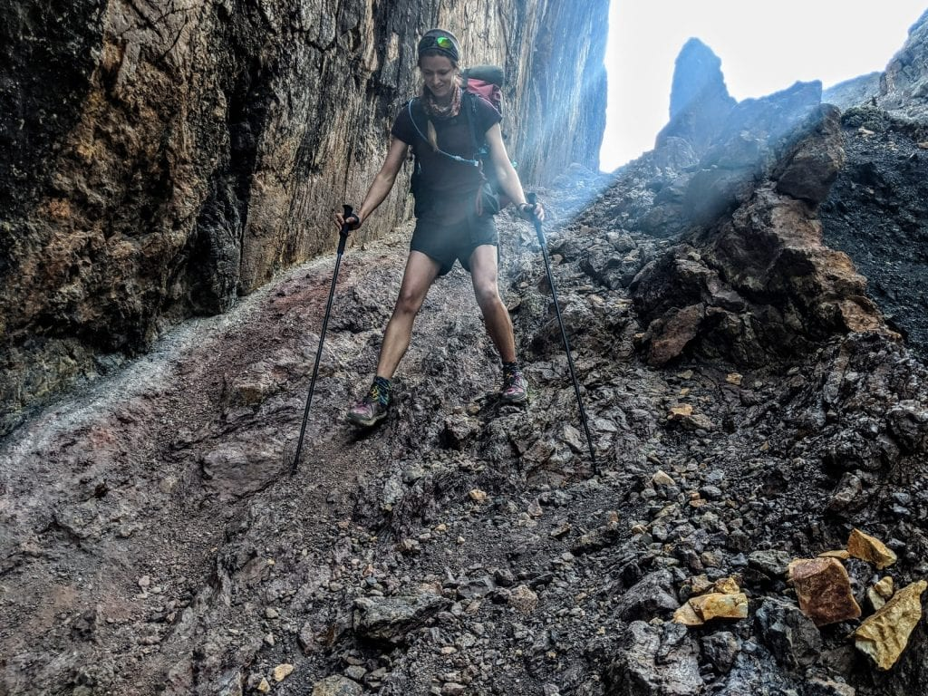 Hiker uses trekking poles to descend slippery trail