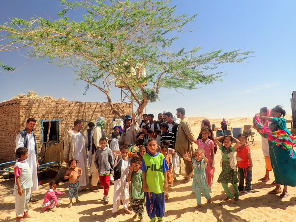 Large family outside mud hut in Sudan desert waving and smiling