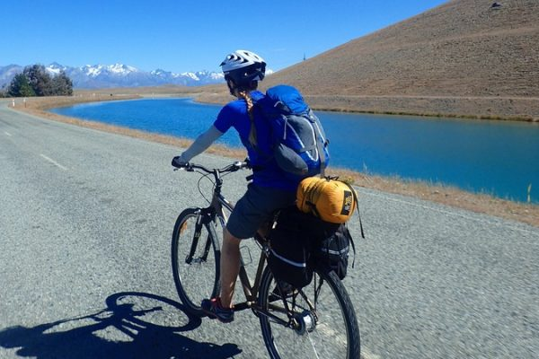 Touring cyclist rides beside canal in New Zealand