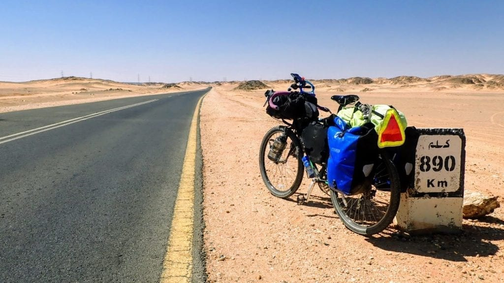 Touring bicycle leans against km marker on desert highway in Sudan