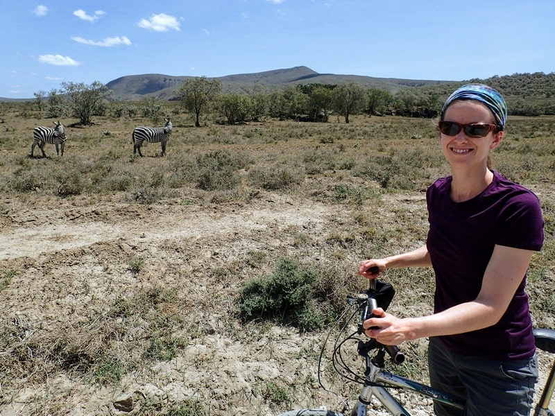 Woman with bicycle and zebras in the background, during cycling safari in Kenya