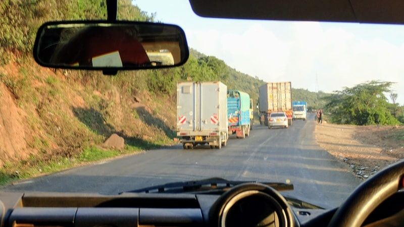 View of highway with several trucks from car window