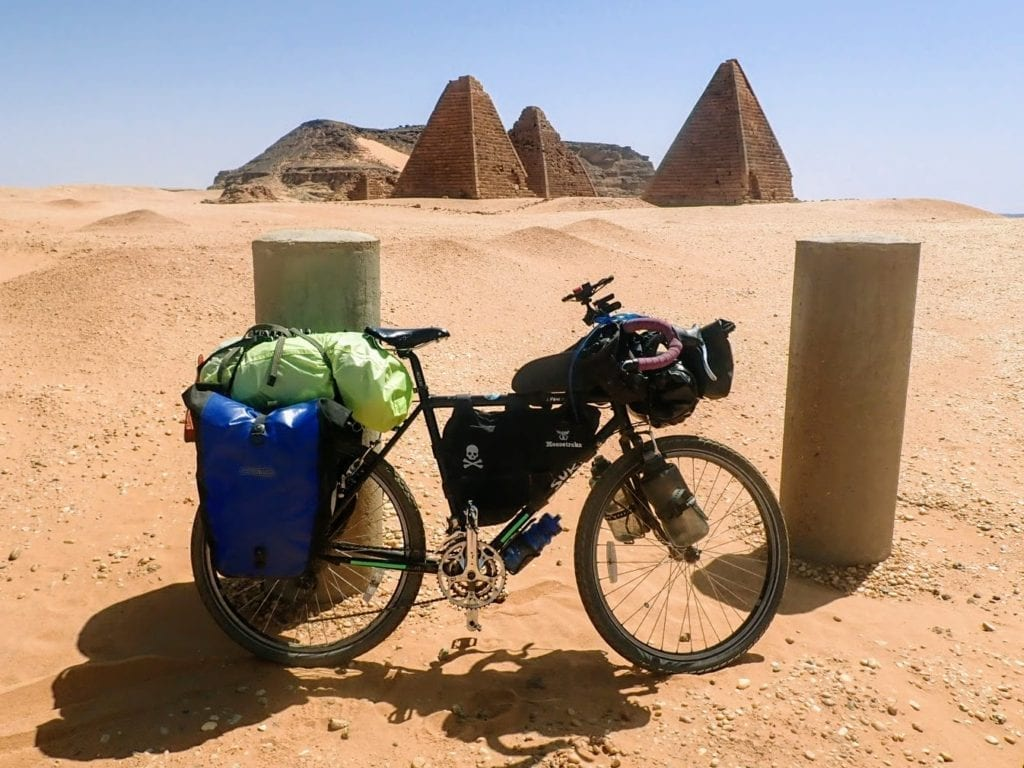 Touring bicycle in front of pyramids in Sudan desert