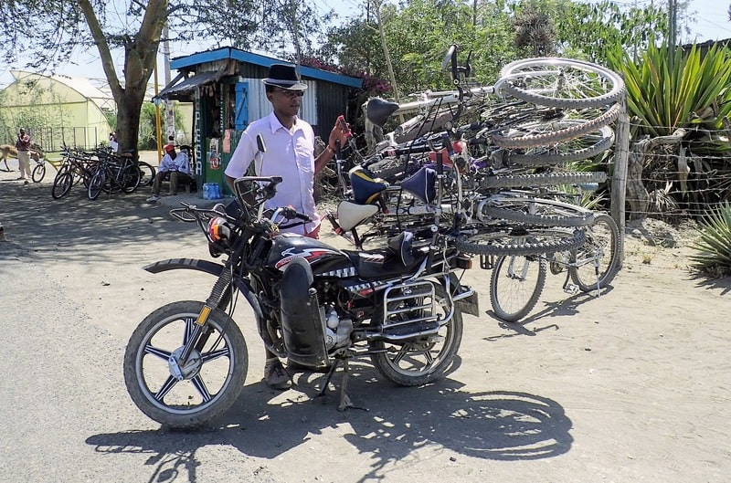 Six bicycles strapped to the back of a motorbike in Kenya