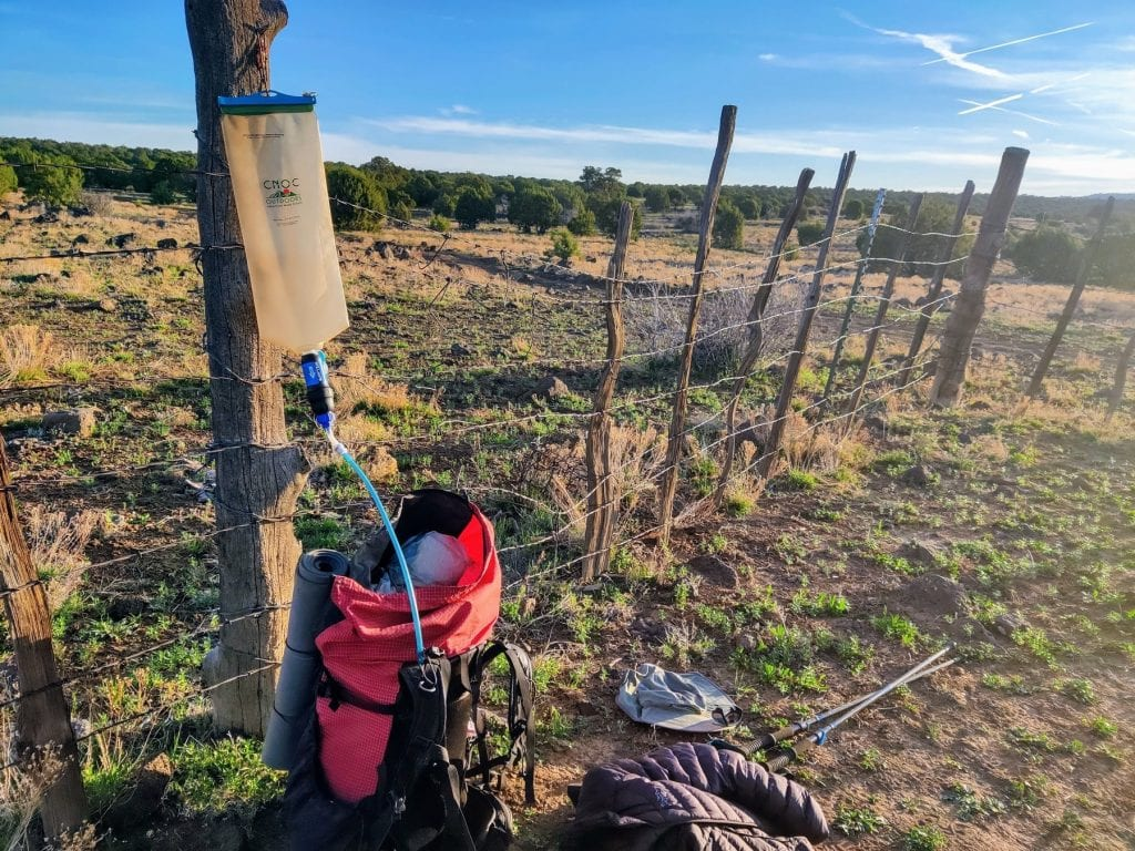 CNOC bag hanging from fence gravity filtering into backpack