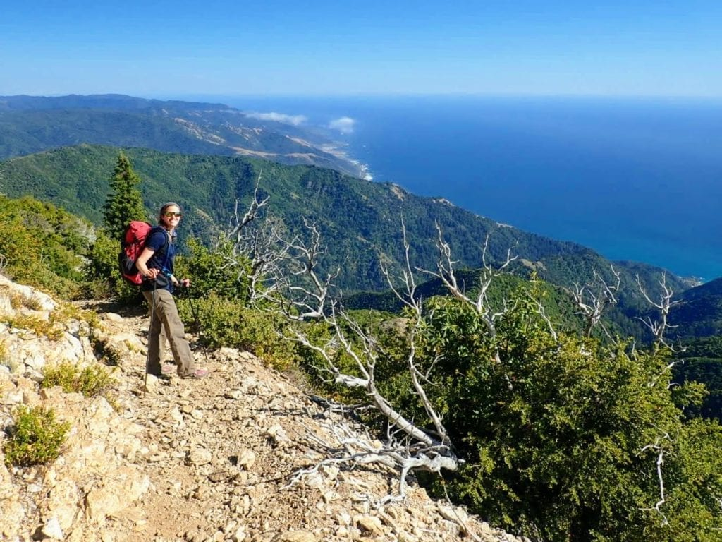 Backpacker on rocky trail with view of ocean beyond