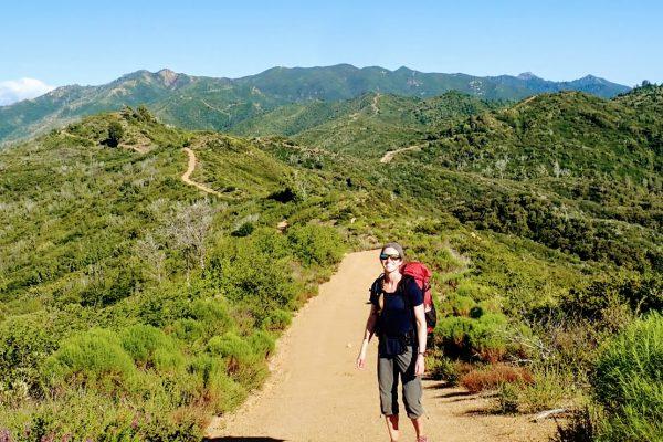 Backpacker on dirt ridge road through green hills