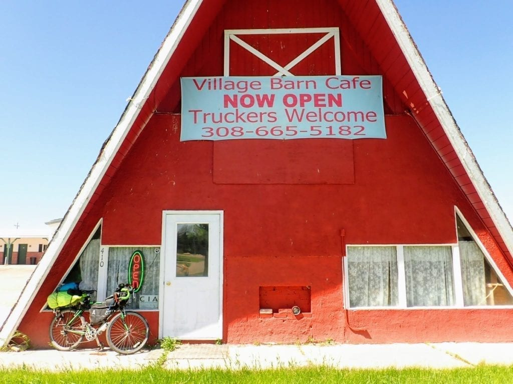 Red triangular cafe with bicycle parked outside