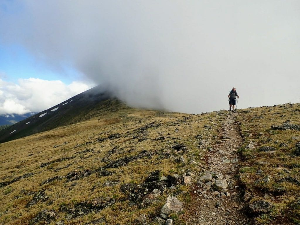 Man hikes in clouds through alpine tundra in Colorado