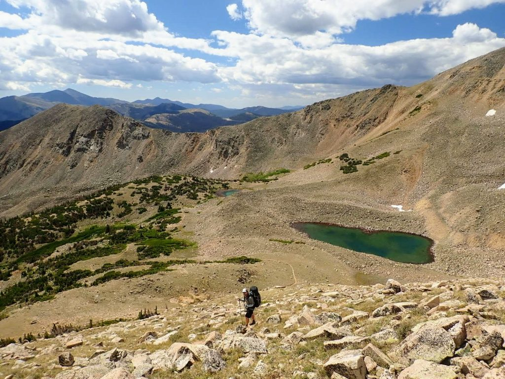 Backpacker climbs high above alpine lake on Collegiate West