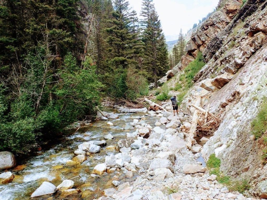 Backpacker hikes on boulders beside river in Elk Creek Drainage, Colorado