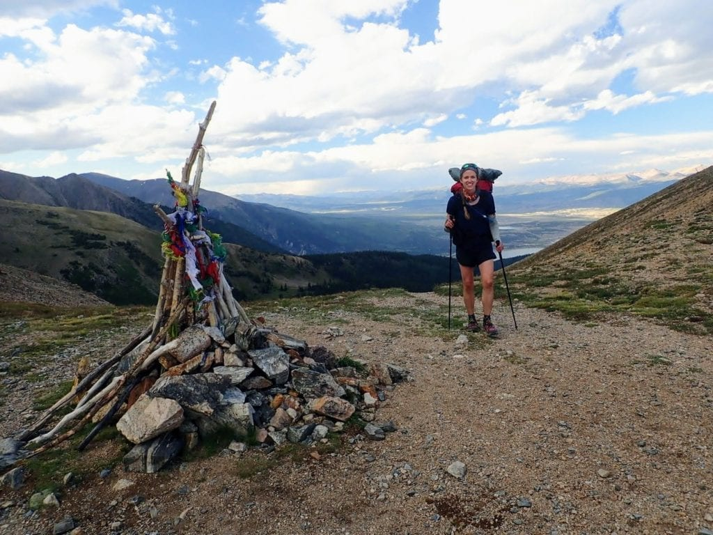 Hiker crests Hope Pass near a summit marker of colored flags