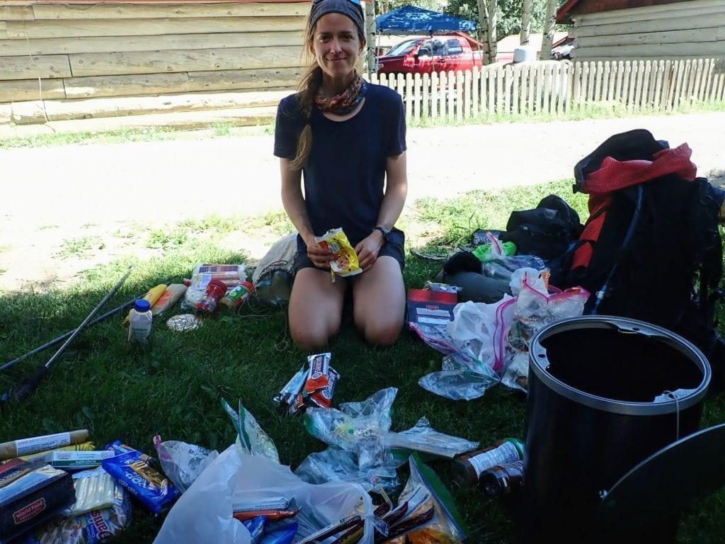 Hiker sorting food in Lake City park while resupplying on the Colorado Trail