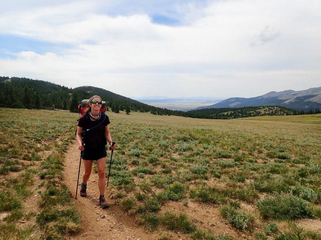 Hiker walks on smooth trail through tundra near Georgia Pass in Colorado