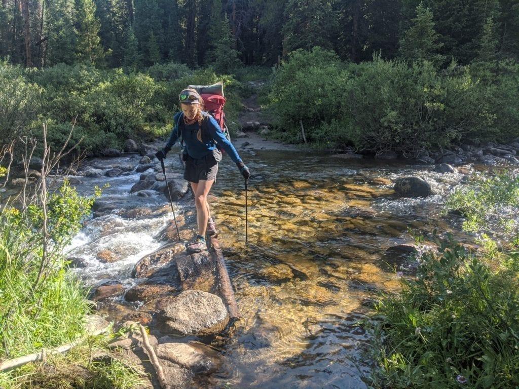 Hiker crosses stream using trekking poles to balance