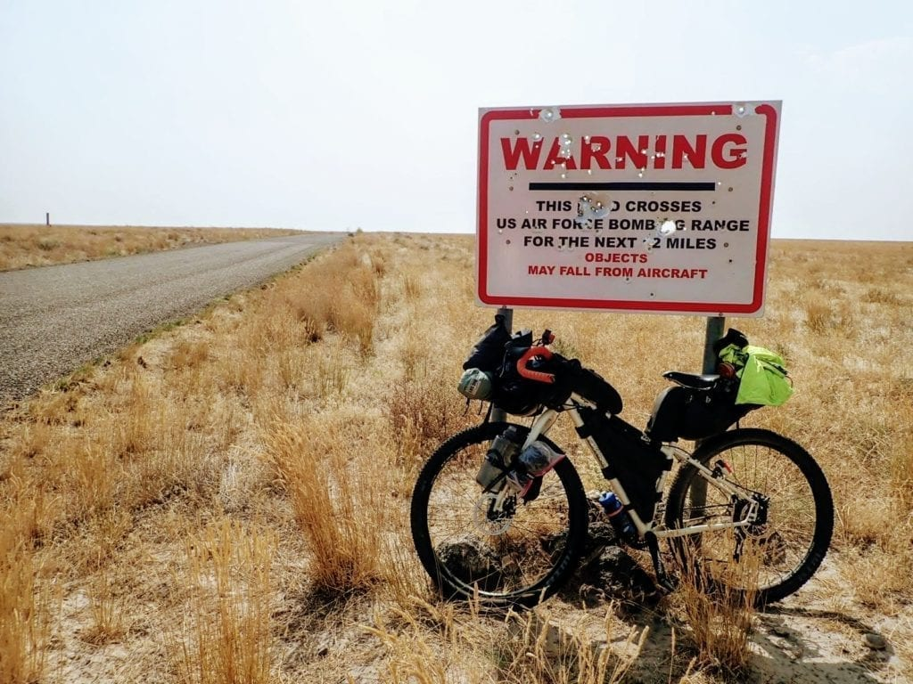 Bike leaning against warning sign that says the road crosses an air force bombing range.