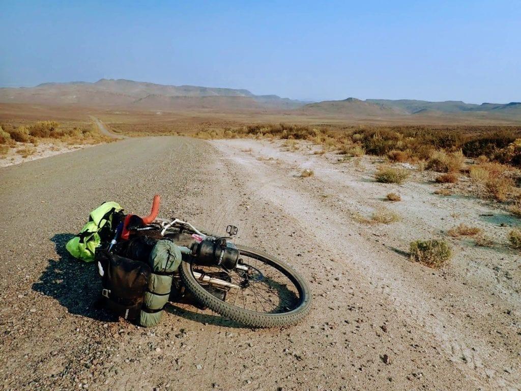 Bikepacking bike lying on gravel road in Nevada desert