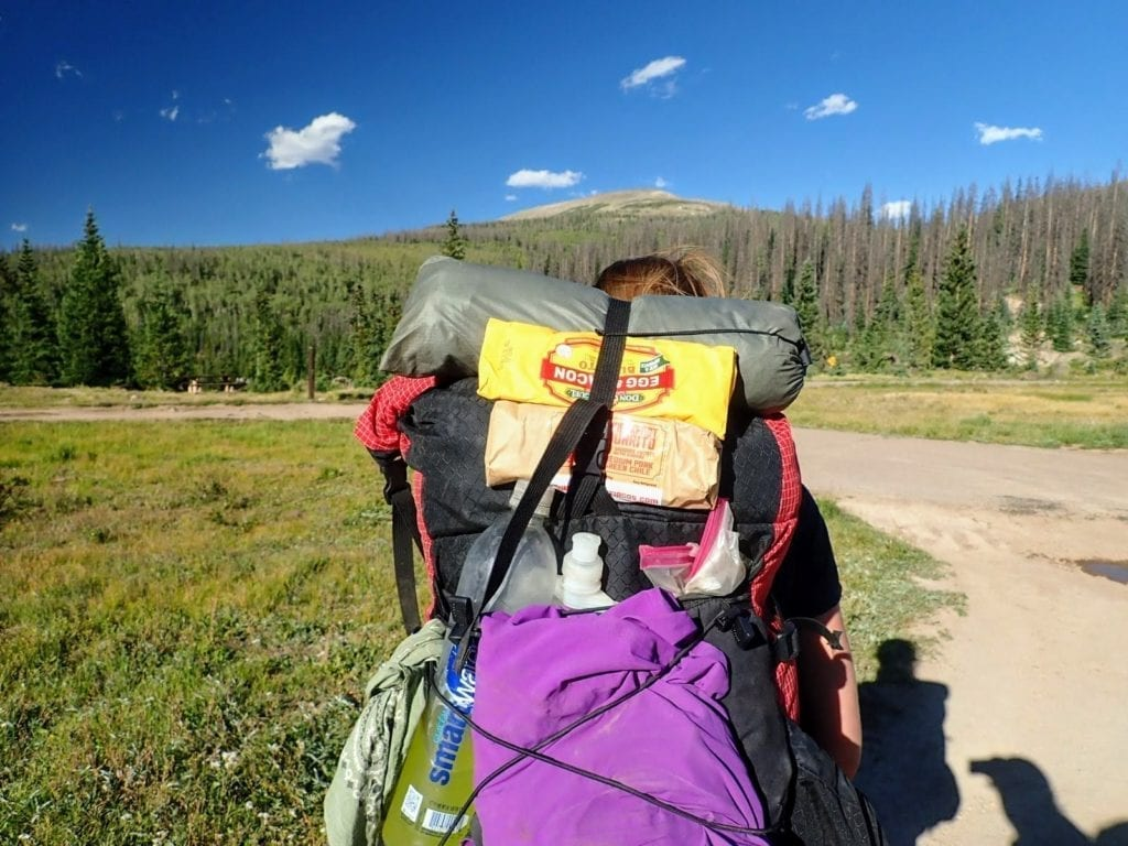 Backpacker carries microwave burritos strapped to pack