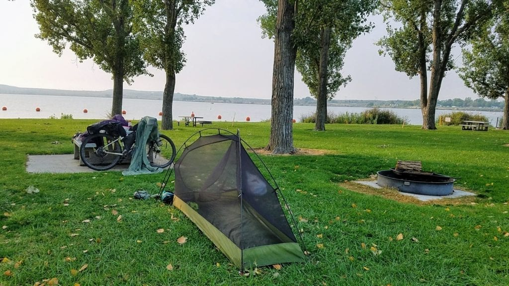 Bicycle and tent at grassy campground by reservoir