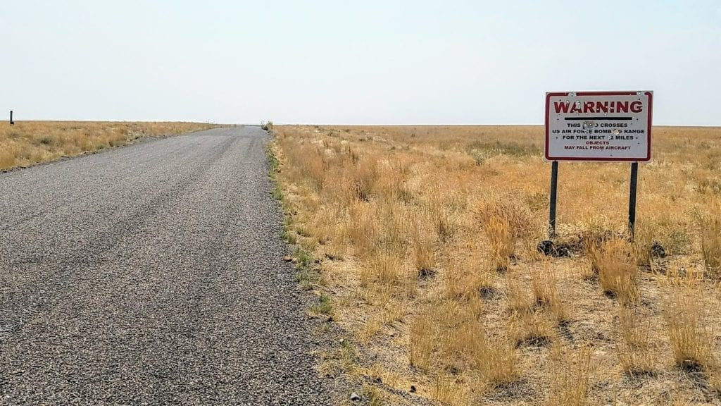 """Warning sign beside gravel road states """"objects may fall from aircraft"""""""