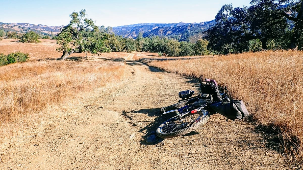 Bicycle lies on dirt road through golden rolling hills in California