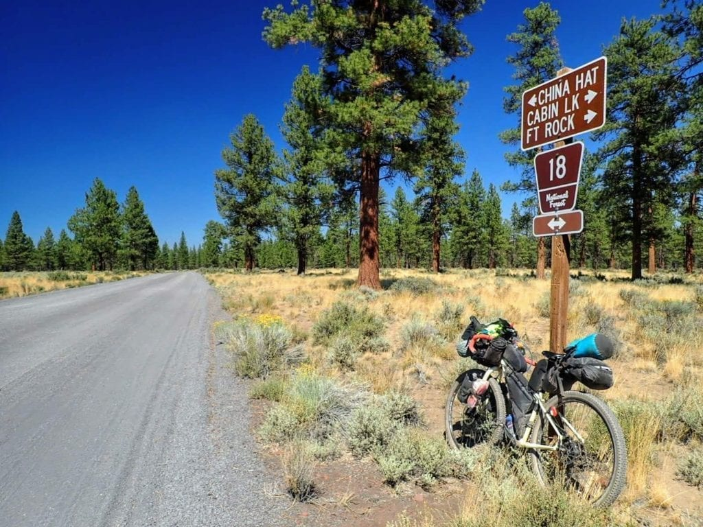 Bike against road sign on gravel forest service road