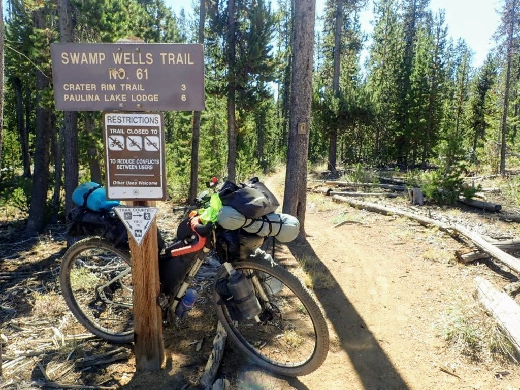 Bikepacking bike leans against trail sign in national forest