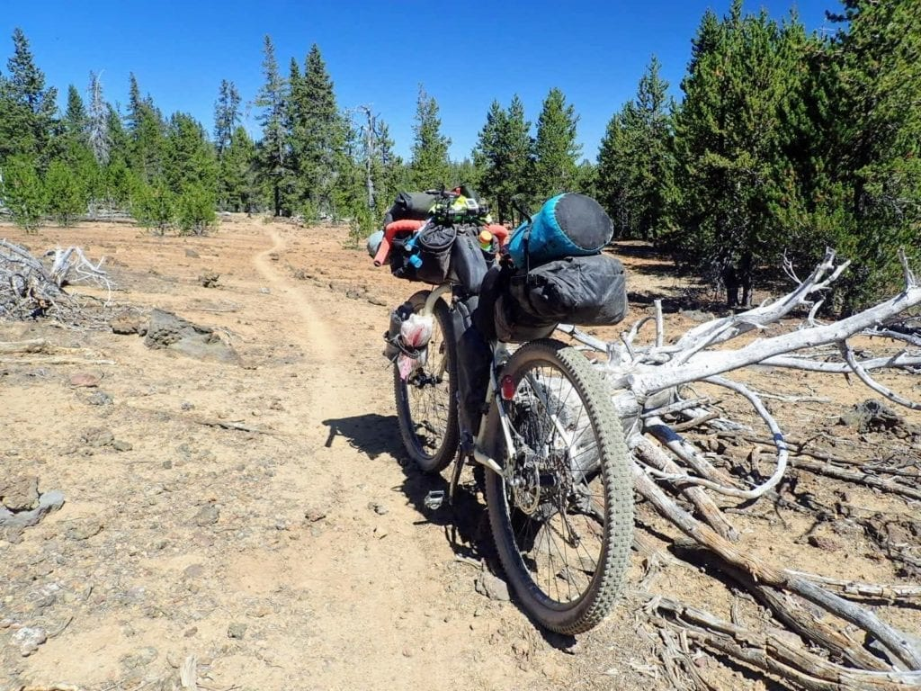 Bikepacking bike on singletrack trail through volcanic landscape
