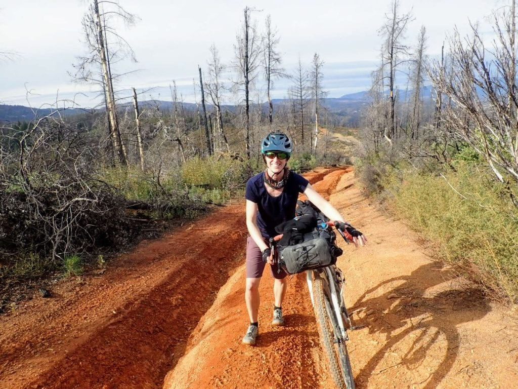 Woman pushes bike up steep ridge road while bikepacking in Mendocino National Forest